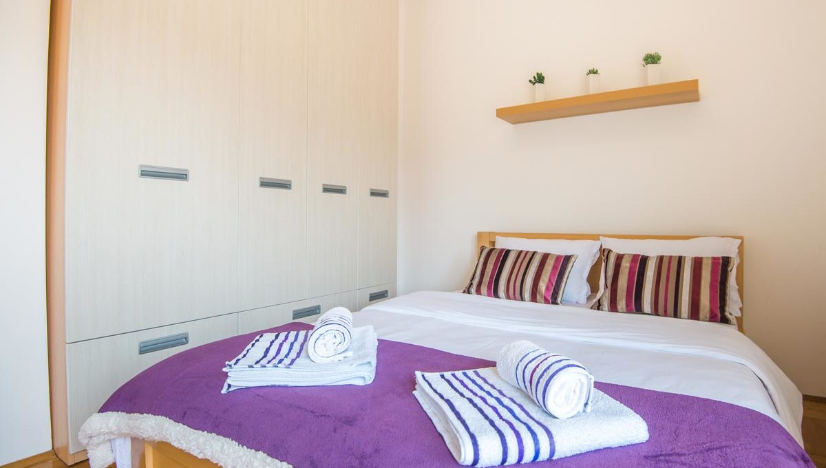 Apartment Simpatico doublke bed with purple sheets
