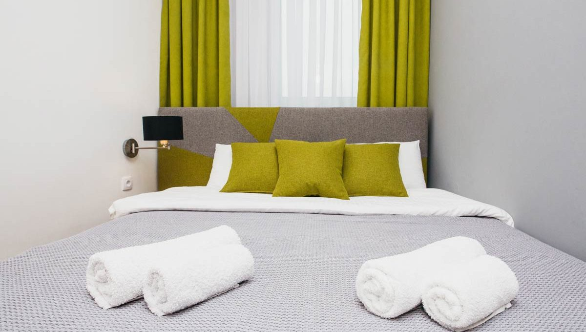Apartment A14 double bed with green pillows